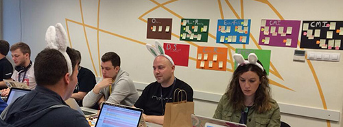 Sprinters at DevDays Szeged wearing bunny ears, in front of colored issue charts.
