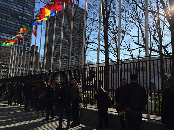 Camp attendees line up outside the UN, under the flags of many nations.
